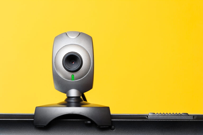 Best webcam with microphone in india placed above the laptop with yellow background